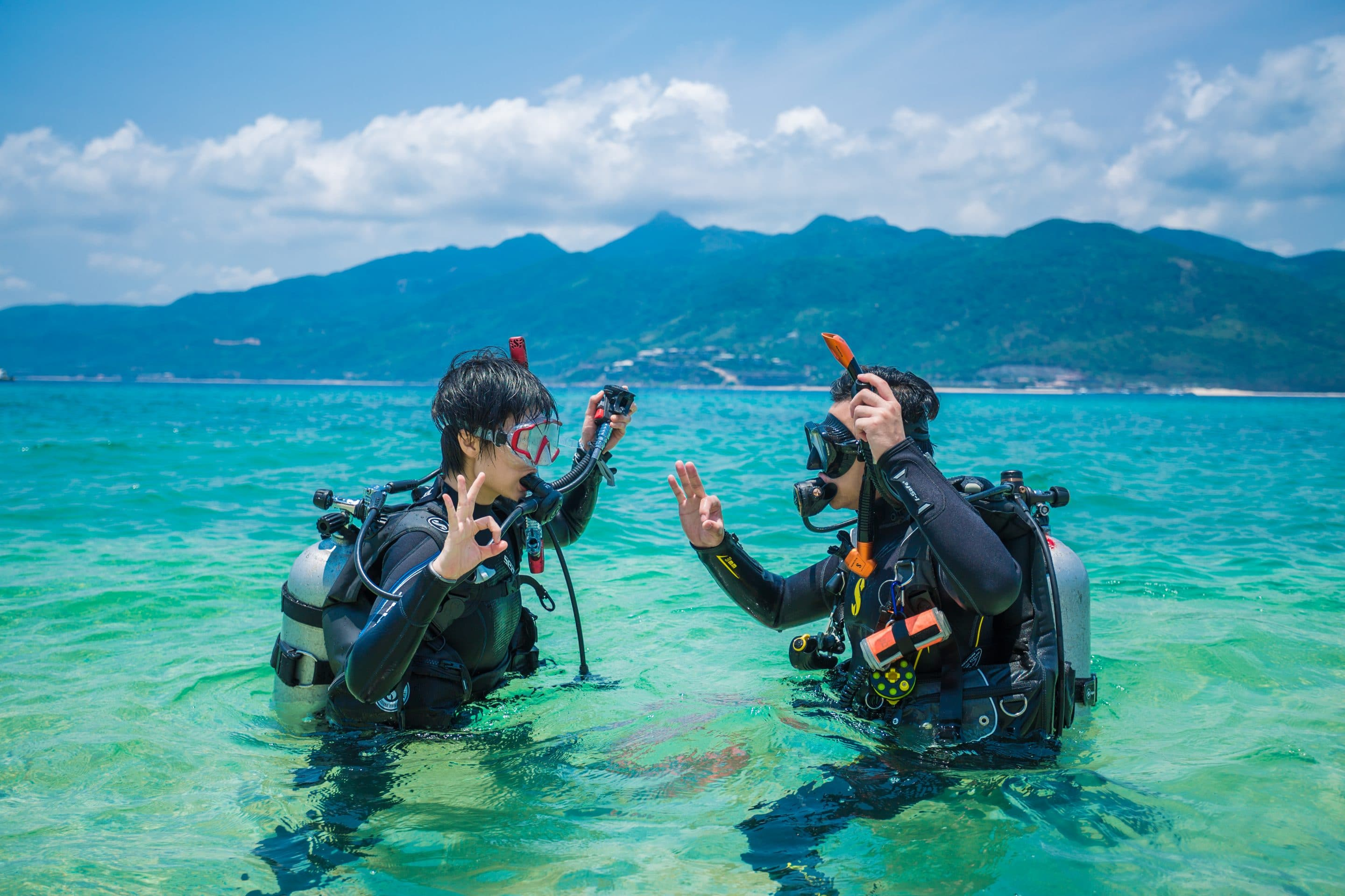 Two people practice scuba diving standing in water