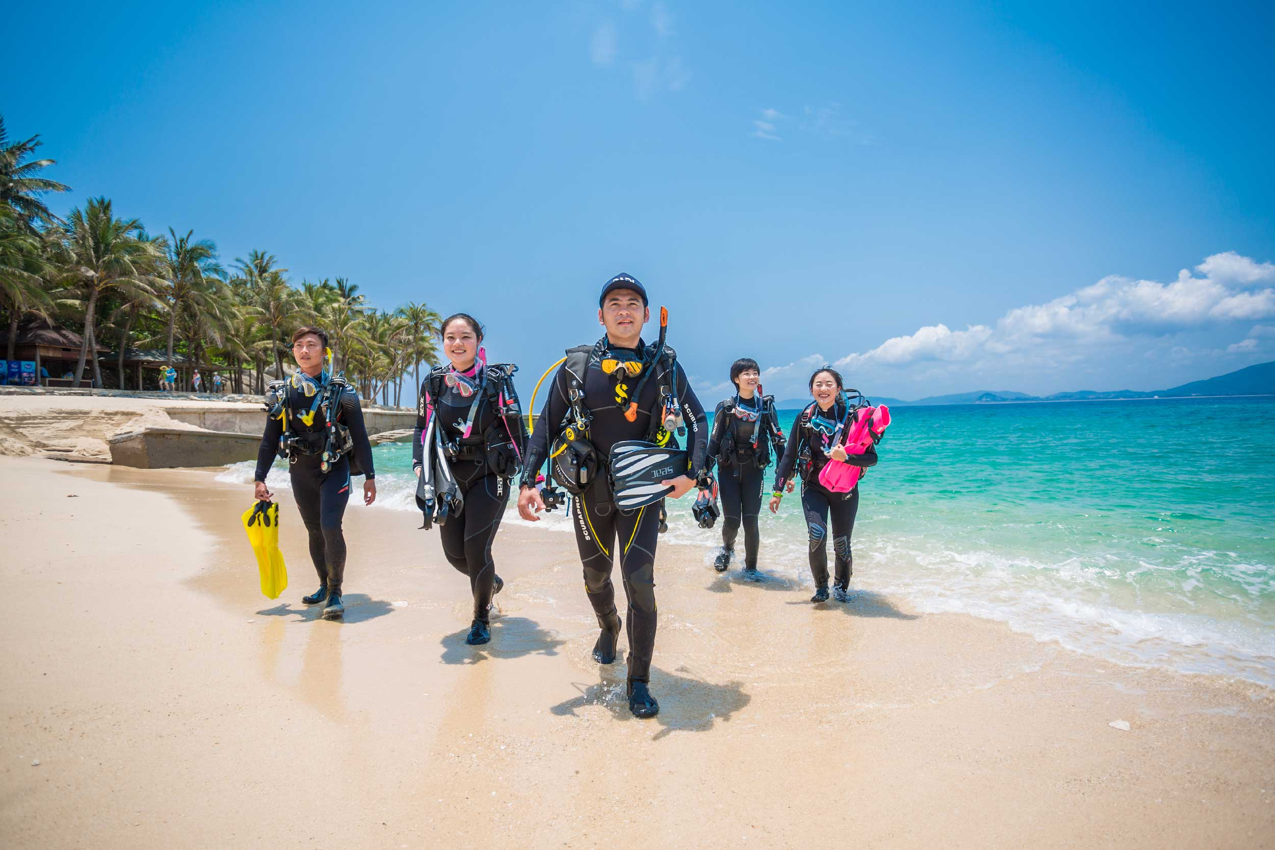 PADI Scuba divers walking out of the water wearing scuba diving equipment