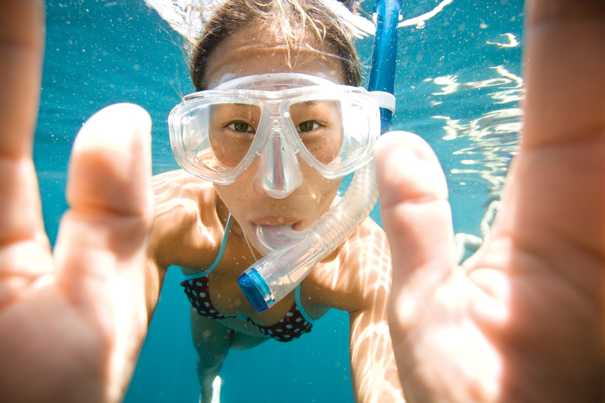 Woman snorkeling underwater looking into the camera