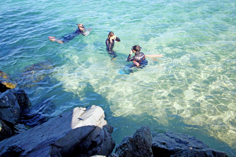 Three people snorkeling in shallow water near rocks
